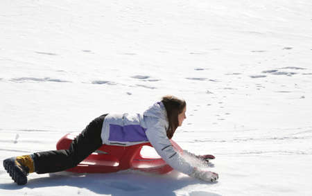 little girl goes down with a sled and goes fast and laughs Standard-Bild - 102794951