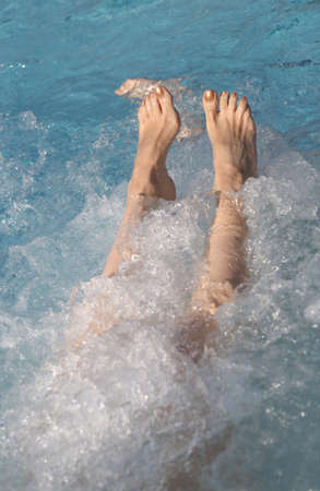 feet of a woman who relaxes in the whirlpool of a swimming pool