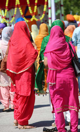Two young sikh women with colored dress in the street