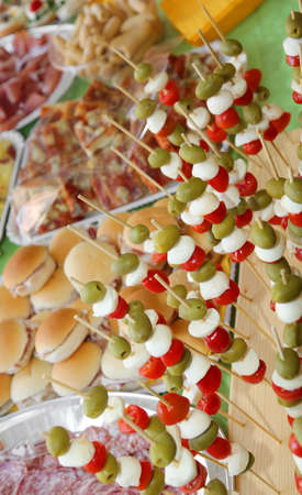 Many skewers with olives, mozzarella cheese of bufala, mortadella and red tomatoes and a lot of foods at the party