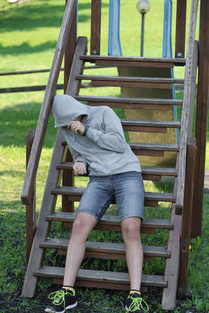 Drug addict who has just got a dose of drugs, hides with the hood of the sweatshirt leaning against a slide in a playground in the public park