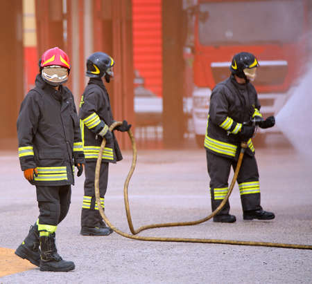Firefighters team during the extinguishing of a fire with foam Stock Photo