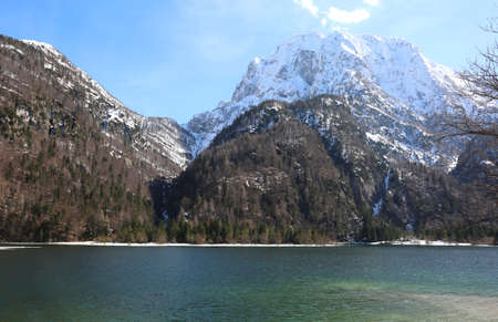 Awesome alpine little lake called Predil Lake Northern Italy near Austrian border with snowed mountains