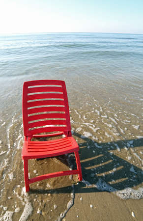 red beach chair in the middle of the blue sea waves