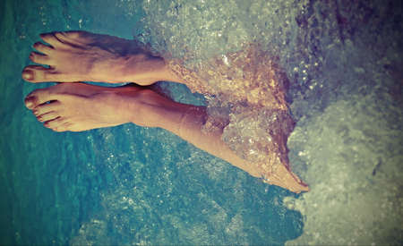 legs of a lady who relaxes in the hot tub of a swimming pool in a tourist village Stock Photo