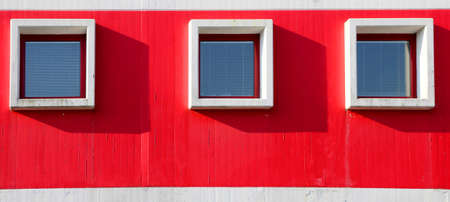 three square windows in the building with red wall