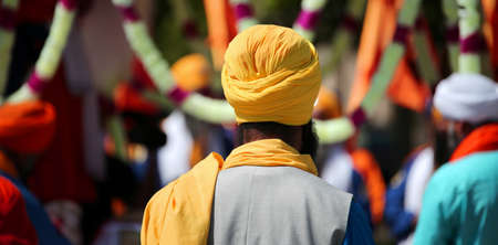 Sikh man with yellow turban during the religious rite in the city Stock Photo