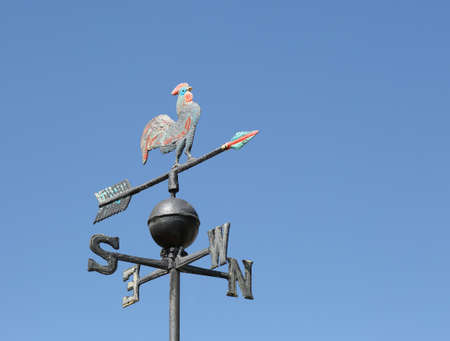 Old wind vane to detect the wind direction with the arrow pointing towards the cardinal point where the winds blow