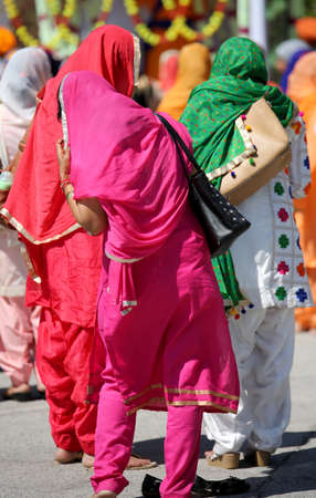 many sikh women with colored dress in the street during religious celebration Stock fotó