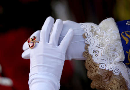 Man and Woman with white gloves and the lady with a precious ring with red gems