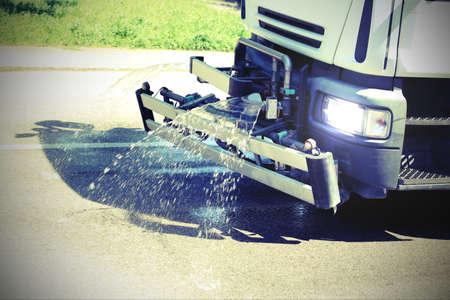 Large roadwashing truck while spraying water on the asphalt