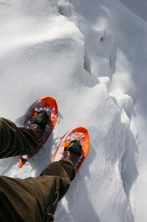 Reckless hiker with orange snowshoes and velvet pants on the edge of a crevasse in the glacier in the mountains Stock Photo