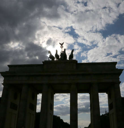 Backlit Brandenburg Gate in Berlin Germany  with the silhouette of four horses and tall columns with cloudy skies Stock Photo