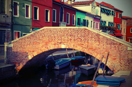 brick bridge over the navigable channel island of Burano in northern Italy near Venice with vintage effect Editorial