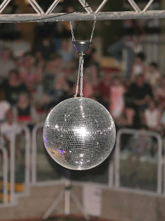 Big disco ball at the concert that reflects light directed at it in many directions Фото со стока