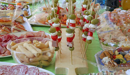 Italian Caprese skewers with tomato mozzarella green olives and more foods like sandwiches and salami at party