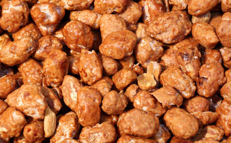 Background of toasted peanuts coated with sweet caramel for sale in the candy store