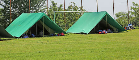 two green tents mounted in a meadow by the scouts for their camp Imagens - 104453420
