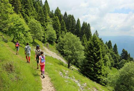 vierköpfige Familie spaziert auf dem Weg in die Berge