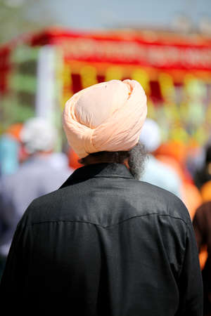Sikh man with black shirt and turban during religious rite outdoors Stock Photo