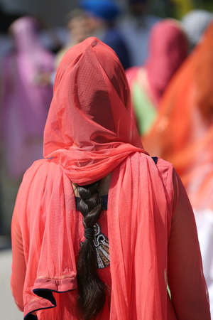 sikh woman with long black hair and red dress during the cerimony