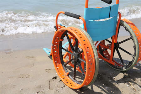 orange wheelchair used to help disabled people get to the sea