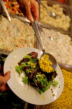 self-service restaurant customer serves with a spoon and puts lettuce and corn in the dish Stok Fotoğraf