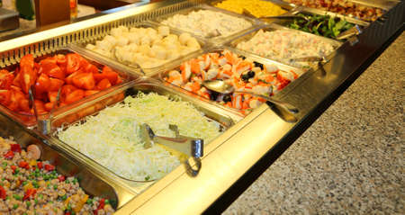 trays with vegetables and raw fish in a Chinese self-service restaurant