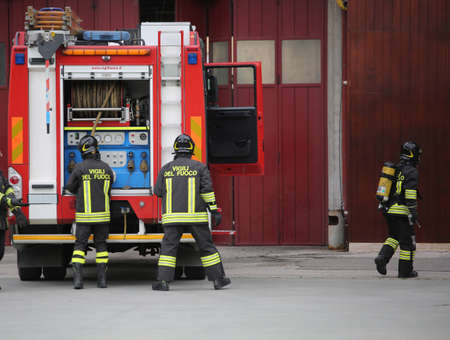 Italia, IT, Italy - May 10, 2018: big fire truck and three talian firefighters with uniform during drill at fire station Redakční