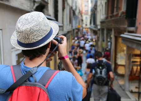 Young photographer with digital camera and big hat takes many photos in Venice in Italy Stock Photo - 106134931