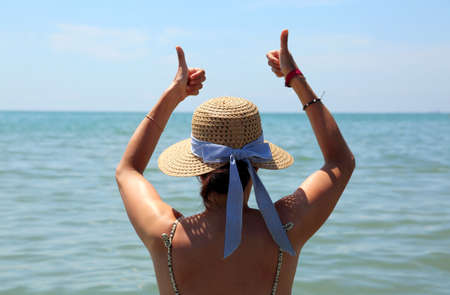 young woman with straw hat and thumbs up in ok sign is all right at the sea in summer Foto de archivo