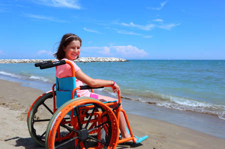 caucasian little girl on the wheelchair on summer by the sea Standard-Bild