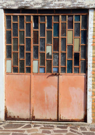 very old glass door of a workshop with glasses in the form of rectangles