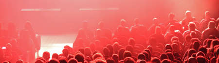 many heads of the paying spectators in the theater during the performance with intentionally blurry effect and with abstract lights Stock Photo