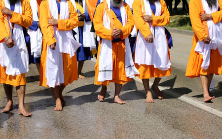 Sikh soldiers dressed in a traditional orange and white dress  walk barefoot during a religious event