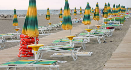 series of closed umbrellas and deck chairs on the beach at the end of the tourist season