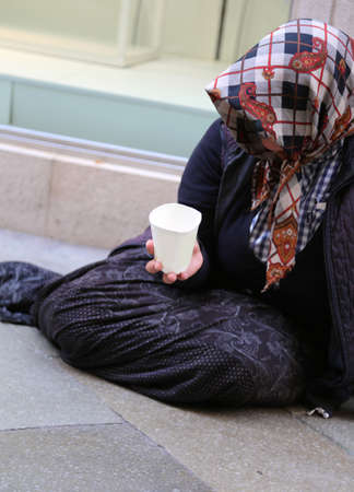 poor old Gypsy woman begs for alms lying in the middle of the city street Stock Photo