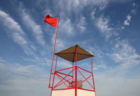 Lifeguard watchtower on the beach with the big red flag waving in the wind Foto de archivo
