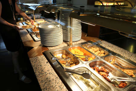 self-service restaurant with many dishes and trays full of food for customers
