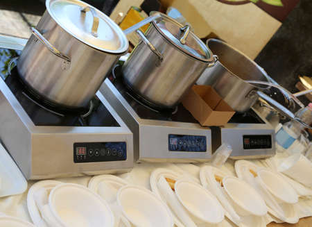 three big pots in the kitchen with plastic dishes