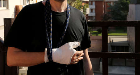 man after the accident with his arm around his neck and his hand fractured with the cast to immobilize the limb Stock Photo
