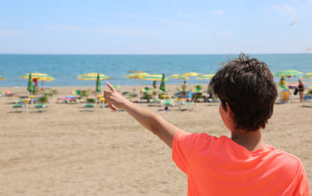 young boy shows the sea from the beach in the summer