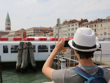 young tourist while photographing the bell tower of san marco in Venice from the boat 스톡 콘텐츠