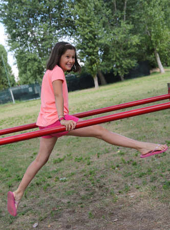pretty little girl doing gym exercises at the bars in the outdoor gym 版權商用圖片