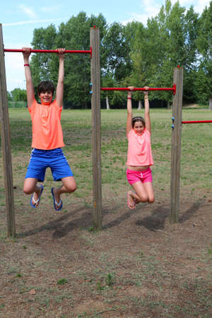two children dressed in a sporty way train themselves doing pull-ups on a training course Stock fotó