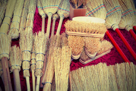 brushes and small brooms in sorghum for sale at market with vintage effect