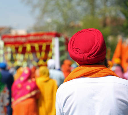 sikh man with red turban during an outdoor parade