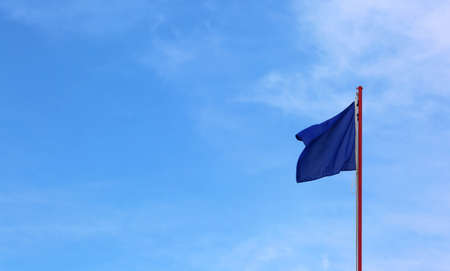 blue flag waves on the blue sky with few clouds