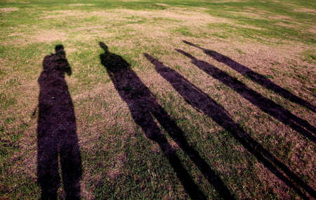 shadows of a family of five persons on the meadow
