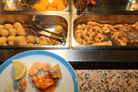tray with many fried foods and shrimps in asian restaurant with a plate